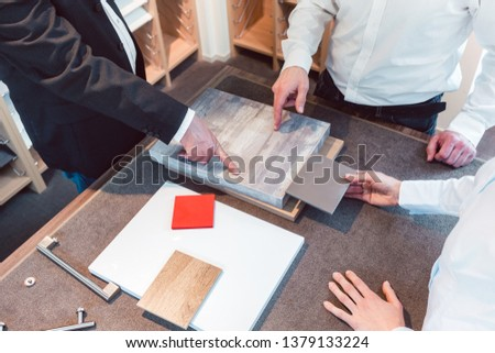 Woman and man with salesman choosing details of their new kitchen Сток-фото © Kzenon