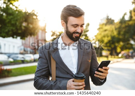 Image of businesslike guys in suits using smartphone while walki Stock photo © deandrobot