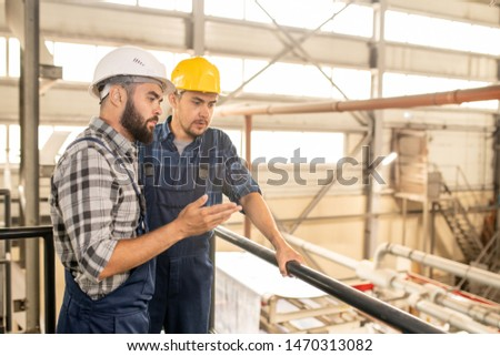 Two young engineers looking at new batch of goods and discussing its quality Stock photo © pressmaster