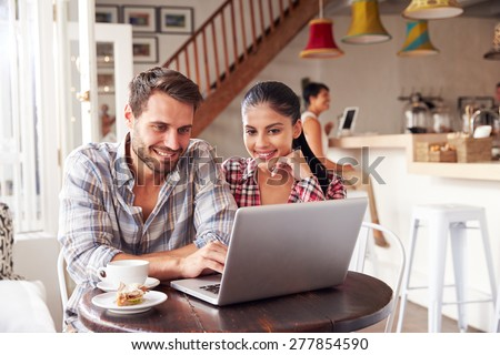 Concentrated young couple in casual clothing sitting on comfortable sofa Stock photo © pressmaster