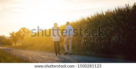 Senior woman and man having a walk along path in the countryside Stock photo © Kzenon