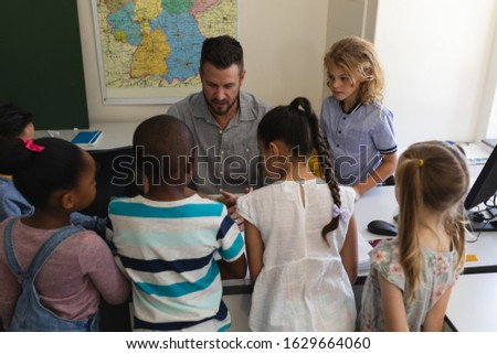 Front view of male school teacher teaching schoolkid on laptop at desk in classroom of elementary sc Stock photo © wavebreak_media