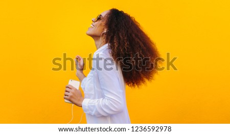 Side view of happy young mixed-race woman with sunglasses looking at camera in poolside on a sunny d Stock photo © wavebreak_media