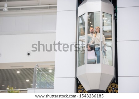 Young couple with paperbags standing in elevator while moving upwards Stock photo © pressmaster
