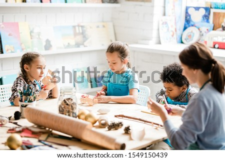 Group of youthful and clever schoolkids and teacher making paper decorations Stock photo © pressmaster