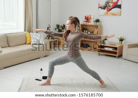 Fit girl in leggins and pullover stretching legs and arms while exercising Stock photo © pressmaster