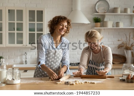 Smiling mother and daughter prepare tasty cookies, girl whisks ingredients in bowl with beater, help Stock photo © vkstudio