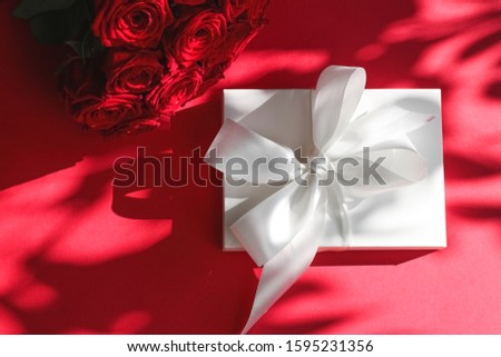 Luxury holiday silk gift box and bouquet of roses on red backgro Stock photo © Anneleven