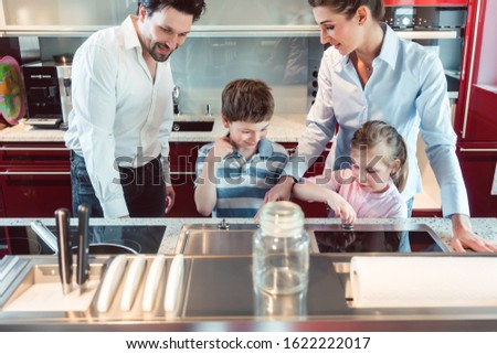 Family testing a new kitchen they intend buying in the showroom Stock photo © Kzenon