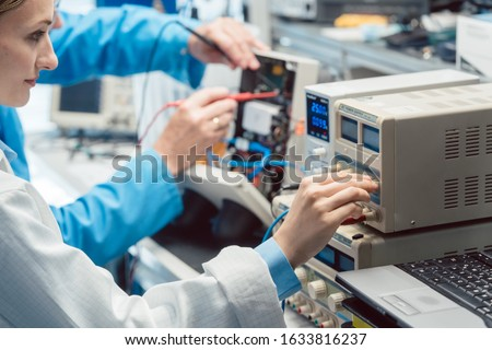 Two electronic engineers on the test bench measuring a new product Stock photo © Kzenon