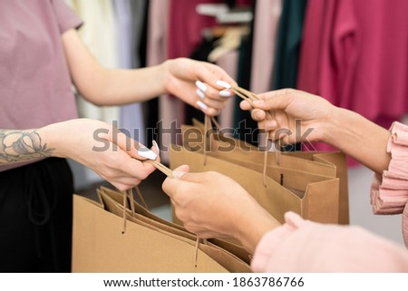 Young shop assistant passing paperbags with new clothes to happy businessman Stock photo © pressmaster