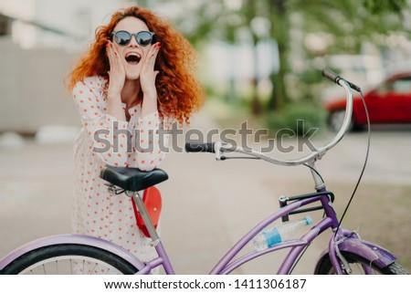 Cheerful female urban biker wears sunglasses and dress, has luxurious crisp foxy hair, keeps elbows  Stock photo © vkstudio