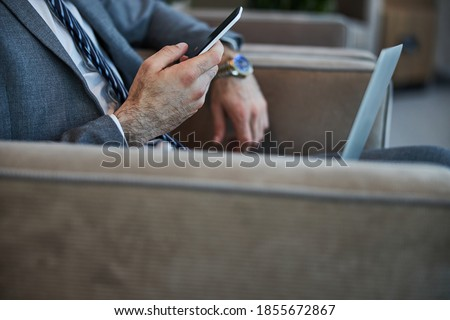 Photo of businessman holding cellphone while sitting on sofa in  Stock photo © deandrobot