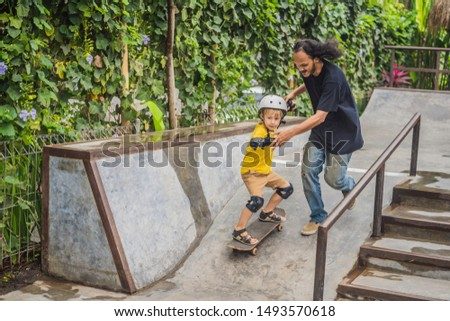 Athletic boy learns to skateboard with asian trainer in a skate park. Children education, sports. Ra Stock photo © galitskaya