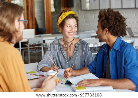 Pretty female student studying with her friends and their workbooks Stock photo © photography33