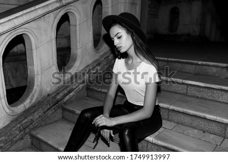 Young woman in a hat and sunglasses seating down on a balcony Stock photo © SophieJames