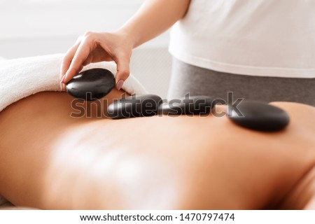 massage therapist placing the hot stones stock photo © sumners