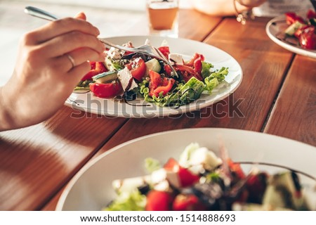 fresh greek salad closeup in a restaurant girl eating in a cafe stock photo © frimufilms