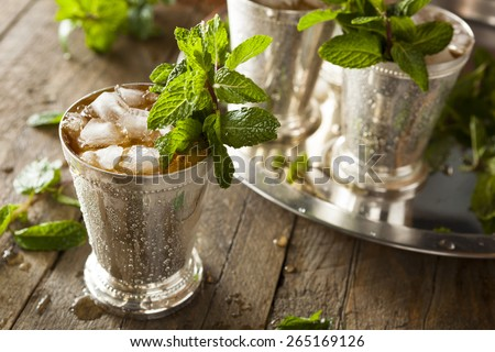 mint julep cocktail with bourbon ice and mint in glass on black background stock photo © yelenayemchuk