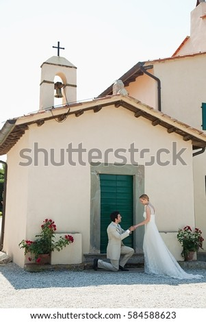 Newlyweds outside church, groom on one knee Stock photo © IS2