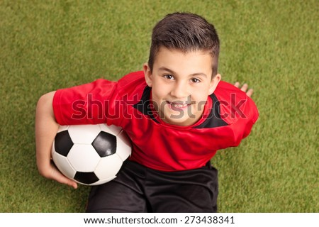 Child sitting on soccer ball on the football pitch. Kid in sports jersey uniform watching soccer tra Stock photo © matimix