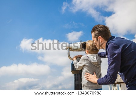 Father and son are looking at Coin-operated binoculars at the sea Stock photo © galitskaya