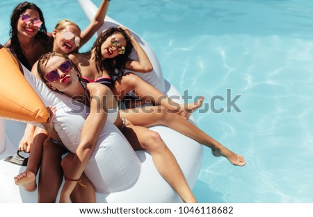 Attractive young woman in bikini sits by the poolside and enjoys Stock photo © boggy