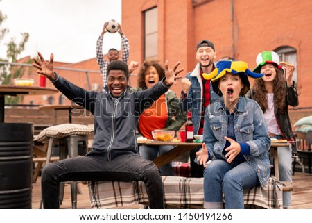 Excited young intercultural friends with beer and snack cheering for their team Stock photo © pressmaster