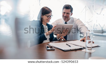 Two professionals sitting by workplace while looking at sample of white wine Stock photo © pressmaster