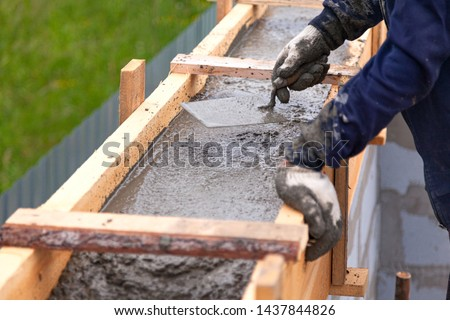 Construction Worker Using Trowel On Wet Cement Forming Coping Ar Stock photo © feverpitch