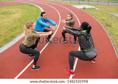 Young intercultural friends stretching their arms forwards while doing squats Stock photo © pressmaster