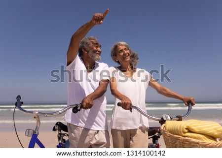 Low angle view of senior man with bicycle pointing at distance on beach in the sunshine Stock photo © wavebreak_media
