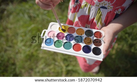 Hand of artist holding small jar of yellow gouache and pouring it on palette Stock photo © pressmaster