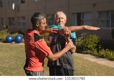 Front view of trainer assisting senior man in performing exercise with dumbbells on exercice ball in Stock photo © wavebreak_media