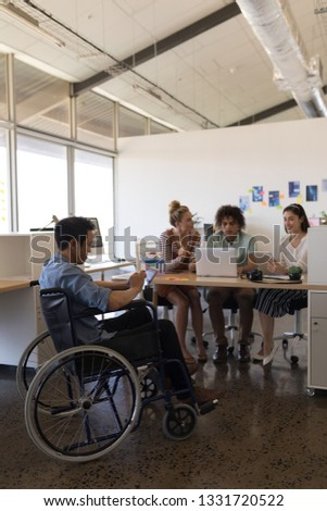 Front view of disabled Asian male executive using digital tablet while multi-ethnic coworkers workin Stock photo © wavebreak_media