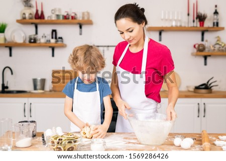 Adorable boy kneading selfmade dough for cookies while helping his mom Stock photo © pressmaster