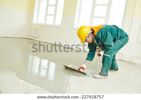 plasterer during floor covering works with self-levelling cement mortar Stock photo © galitskaya