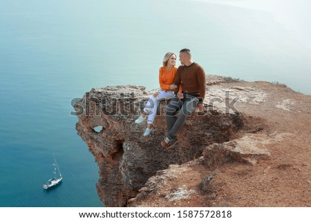 A man and a woman sit on a rock dangling their legs over cliffs Stock photo © ElenaBatkova