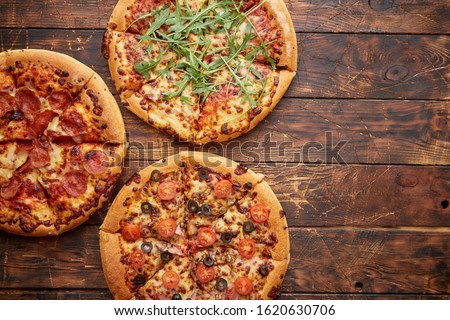 Composition of three various kinds pizzas on wooden table Stock photo © dash