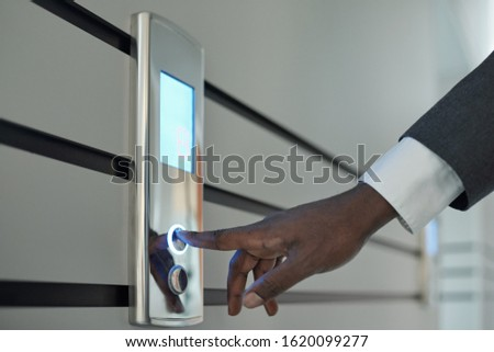 Hand of young African businessman in formalwear pushing elevator call button Stock photo © pressmaster