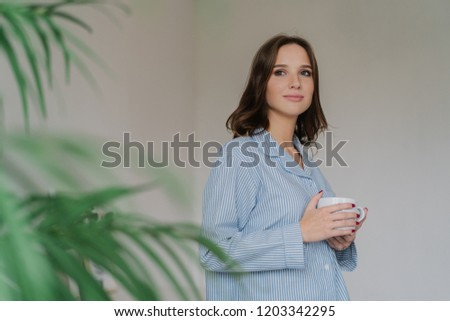 Photo of thoughtful young woman with dark hair, appealing appearance, warms with hot beverage, dress Stock photo © vkstudio