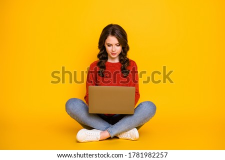 Photo of attractive female model in knitted red sweater, messages online at home, poses on couch in  Stock photo © vkstudio