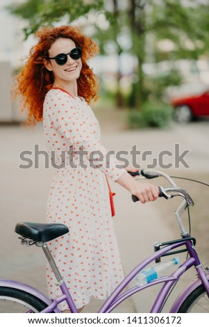 Smiling redhead woman in sunglasses and dress, rides bike through city during summer holidays, has r Stock photo © vkstudio