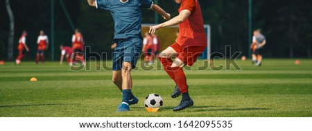 Two Men Kicking Soccer Ball. Junior Teenage Soccer Team on Training Game.  Athletes Running with Bal Stock photo © matimix