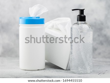 Plastic container with alcohol wipes with hand sanitizer plastic container and box of tissues on lig Stock photo © DenisMArt