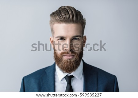Image of handsome bearded businessman posing and looking aside Stock photo © deandrobot