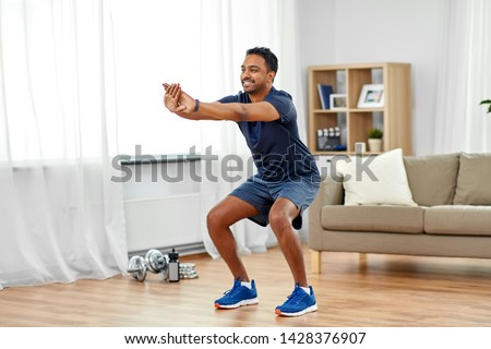 smiling man with fitness tracker exercising at home Stock photo © dolgachov