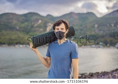 Young man in medical mask performing some workouts in the park during coronavirus quarantine, Corona Stock photo © galitskaya