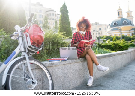 good looking red haired woman reading a book while sitting on her bed stock photo © wavebreak_media