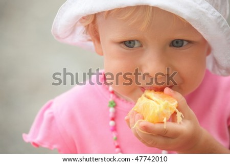 Little girl wearing panama hat is eating orange. focus on right hand. stock photo © Paha_L